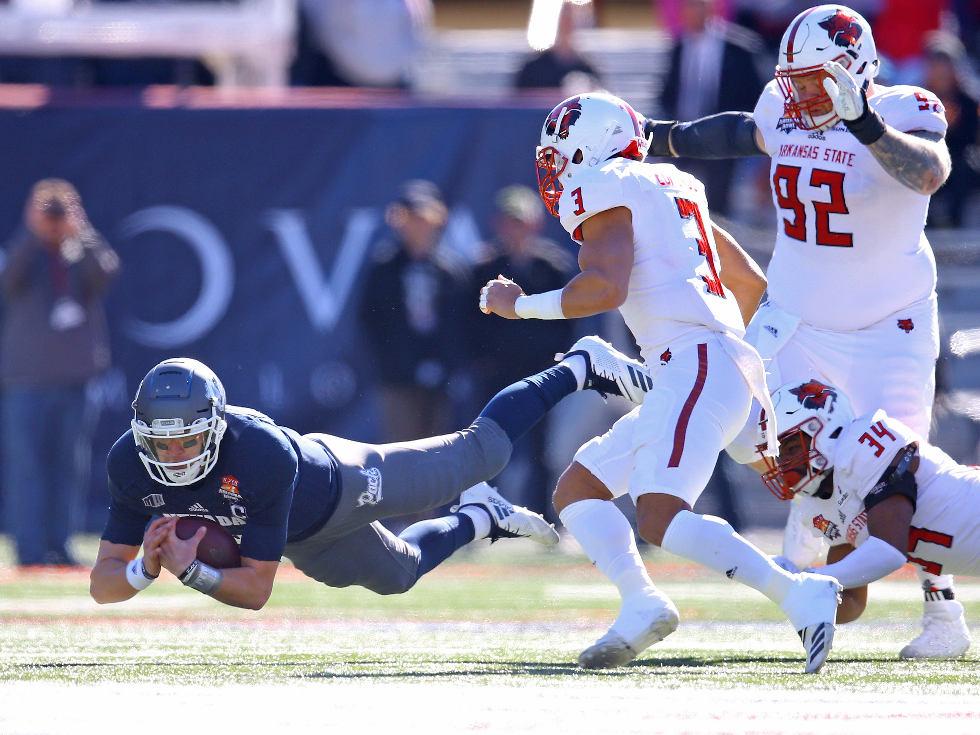 Dec 29, 2018; Tucson, AZ, USA; Nevada Wolf Pack quarterback Ty Gangi (6) dives for yardage against the Arkansas State Red Wolves in the first half of the 2018 Arizona Bowl at Arizona Stadium.