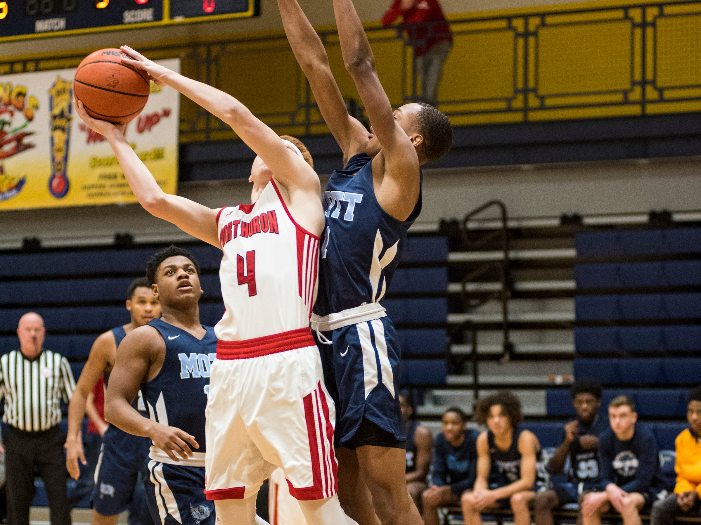 Waterford Mott HIgh School guard Damarion Bonds (right) reaches to block a shot by Port Huron High School guard Ryan Gilbert during their SC4 Holiday Basketball Showcase game Saturday, Dec. 29, 2018 at the SC4 Fieldhouse.