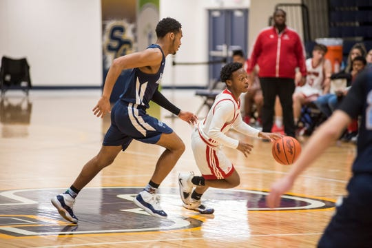 Waterford Mott High School guard Kamariell Manley (left) chases Port Huron High School guard Treshaun Lee as he dribbles the ball during their SC4 Holiday Basketball Showcase game Saturday, Dec. 29, 2018 at the SC4 Fieldhouse.