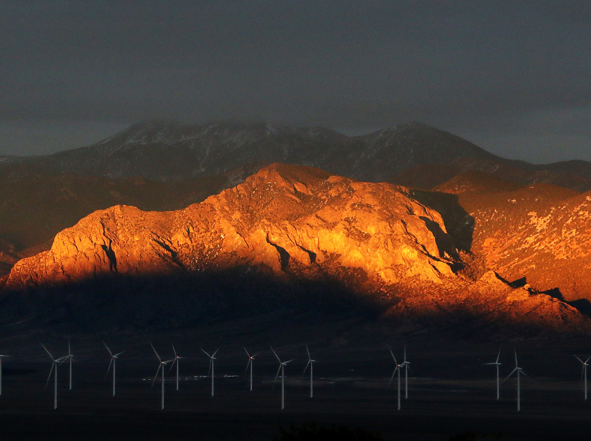 Late evening light is seen illuminating the mountains above the Spring Valley Wind Farm in eastern Nevada on Feb. 1, 2018.