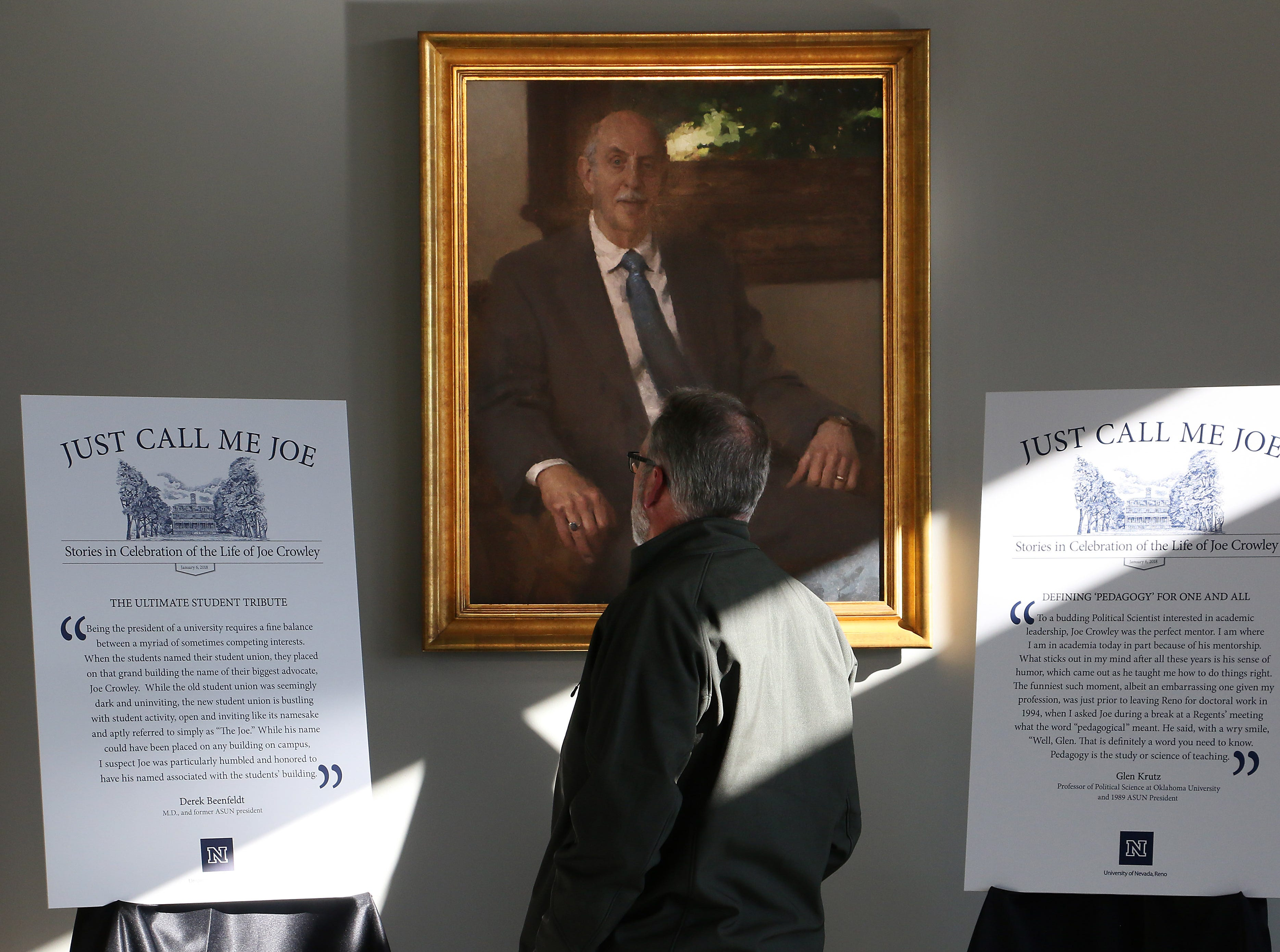 "An attendee stands below a portrait of Joe Crowley during the campus memorial service in honor of Emeritus President Joe Crowley in the Joe Crowley Student Union on the campus of the University of Nevada, Reno on Jan. 6, 2018. The service was called ""Just Call Me Joe: Stories in Celebration of the Life of Joe Crowley."""