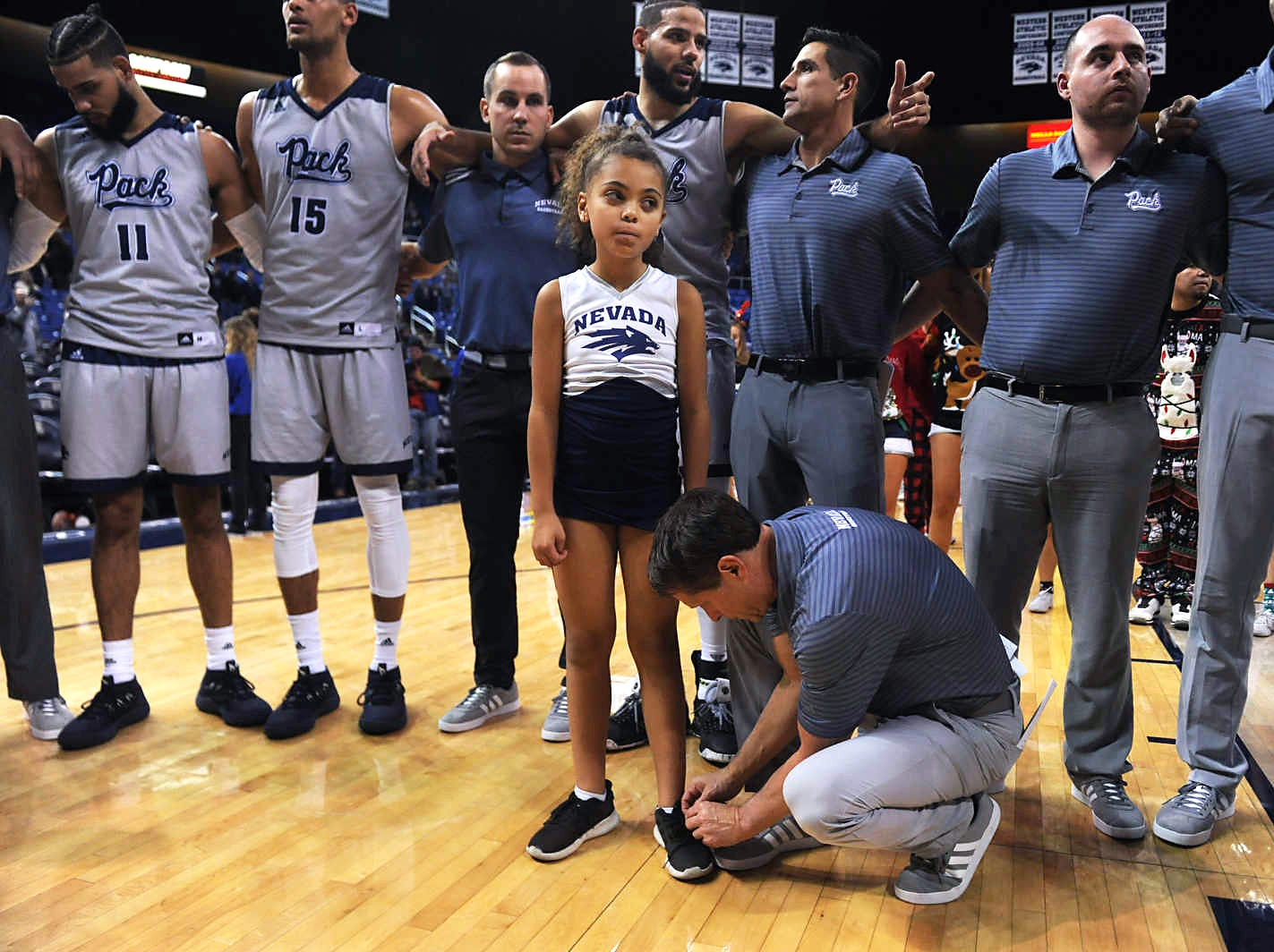 Nevada head coach Eric Musselman ties is daughter's shoe lace directly following their basketball game at Lawlor Events Center in Reno on Dec. 15, 2018.
