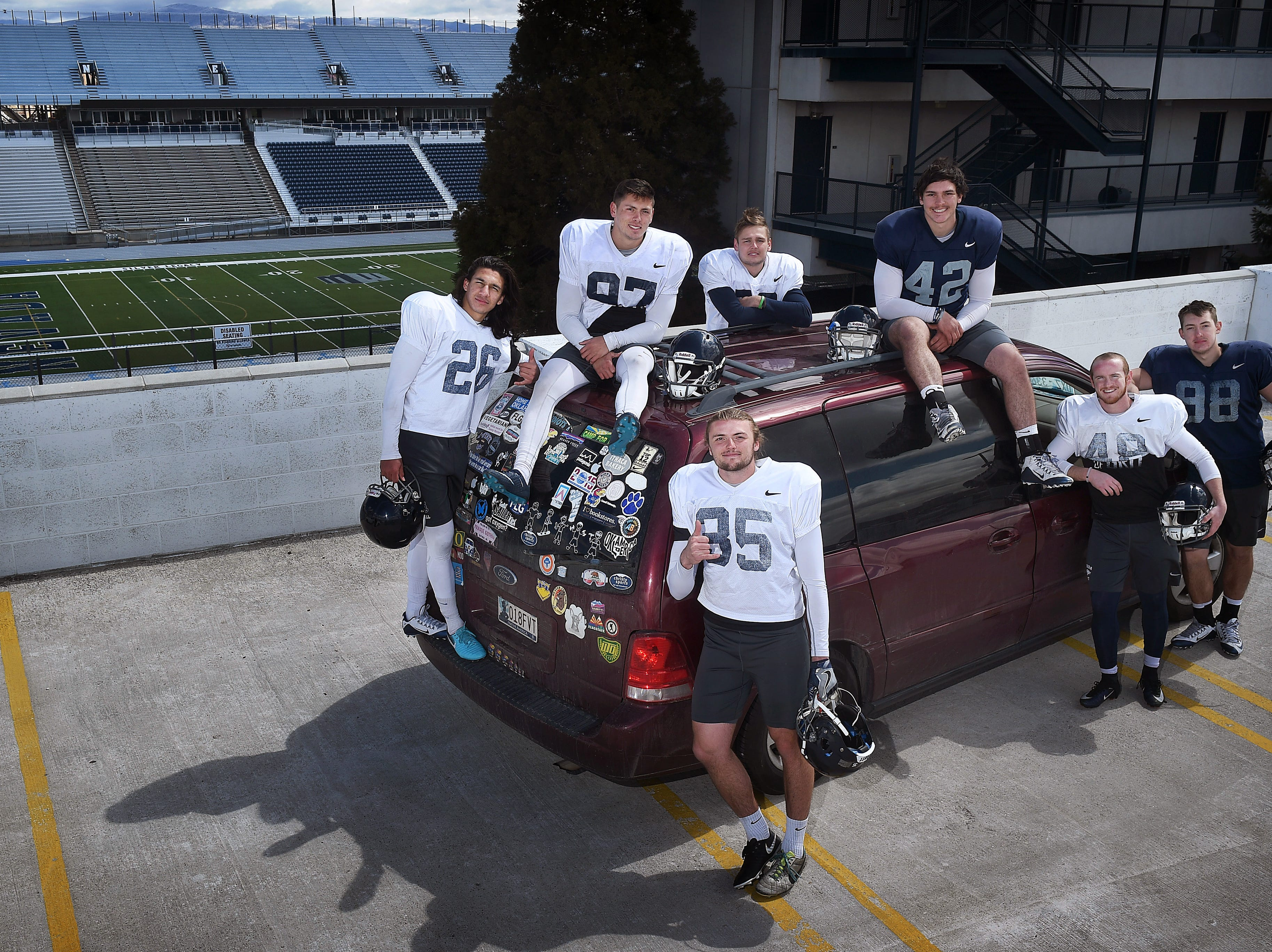 Nevada punter Quinton Conaway, front middle, poses for a portrait with his special teams teammates in front of his minivan next to Mackay Stadium in Reno on April 19, 2018.