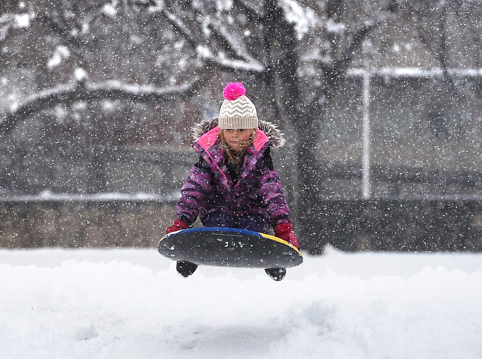 A young girl goes sledding in the fresh snow at Plumas Park in Reno on March 16, 2018.