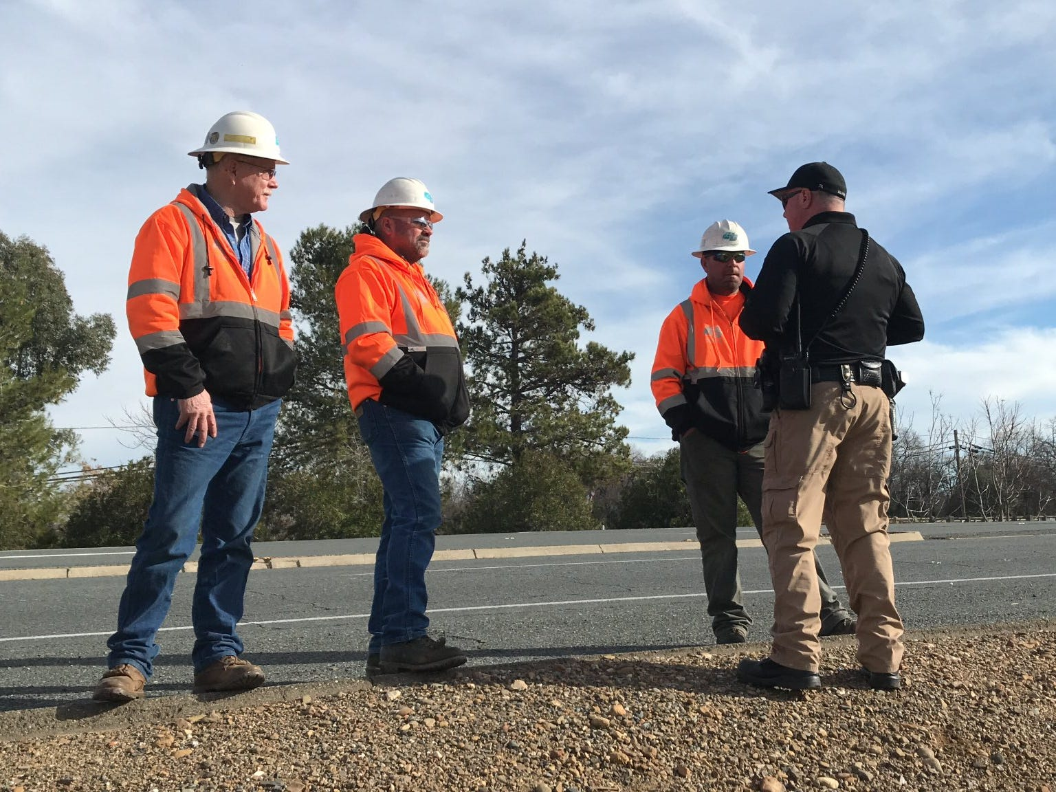 Road workers talk to an Anderson police officer after a shooting on Saturday, Dec. 29, 2018.