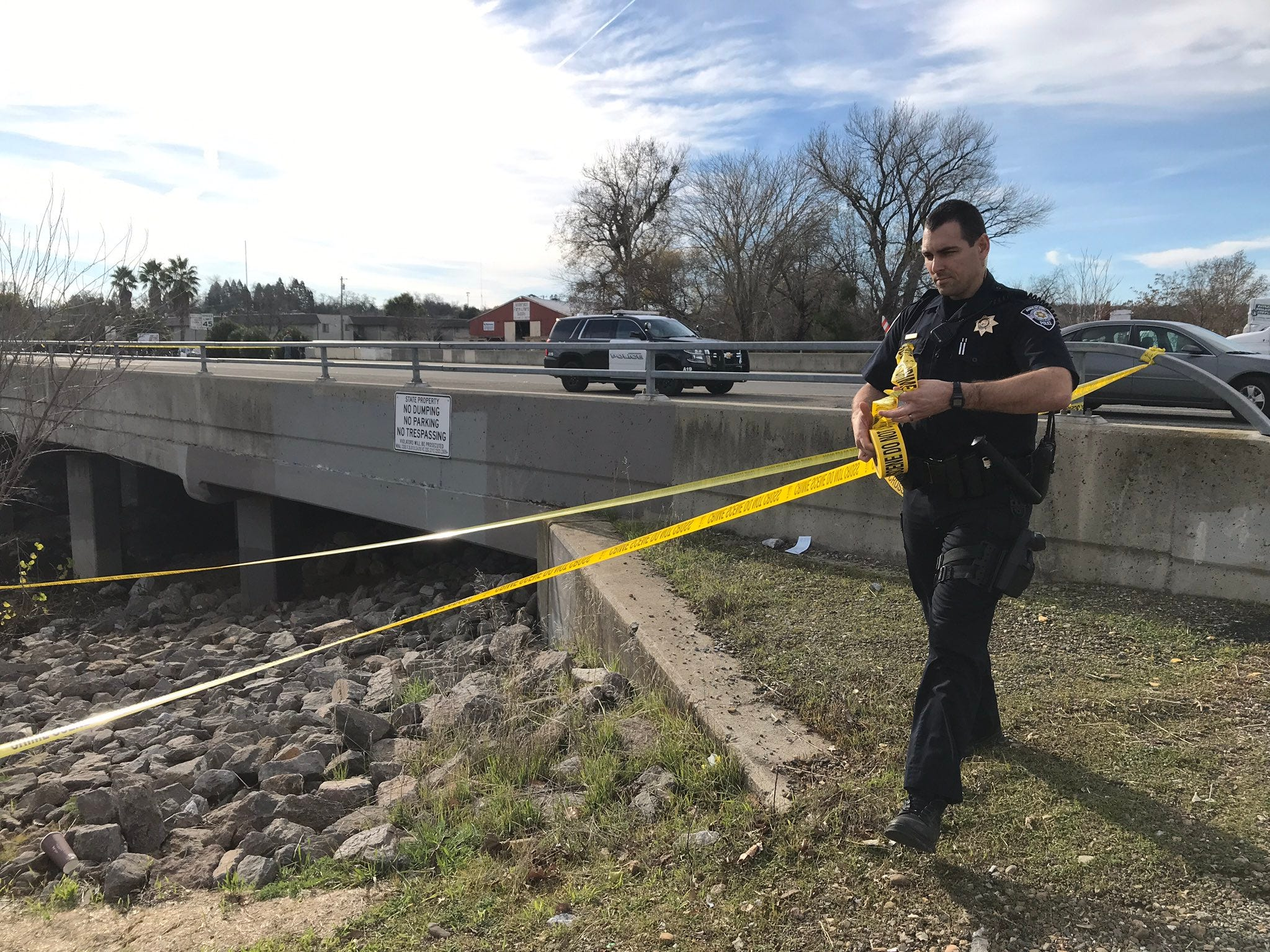 An officer puts up crime tape at a bridge over Anderson Creek while an investigation continued into a K-9 officer-involved shooting near South Street.