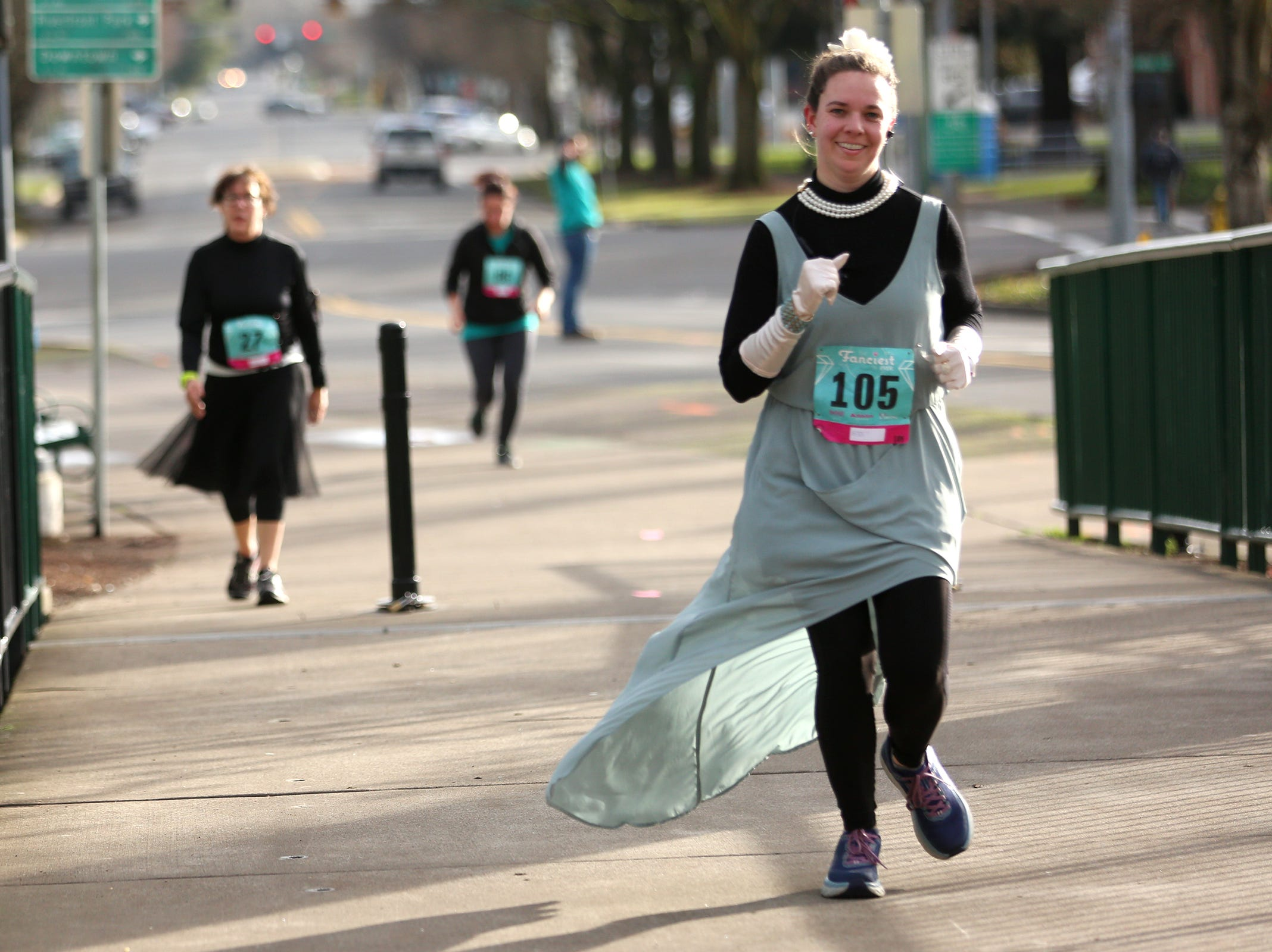 Runners make their way across the Union Street Bridge during The Fanciest 5K. Ever. in Salem on Saturday, Dec. 29. All of the money raised will go directly to advocacy for sex-trafficking survivors in the mid-Willamette Valley.