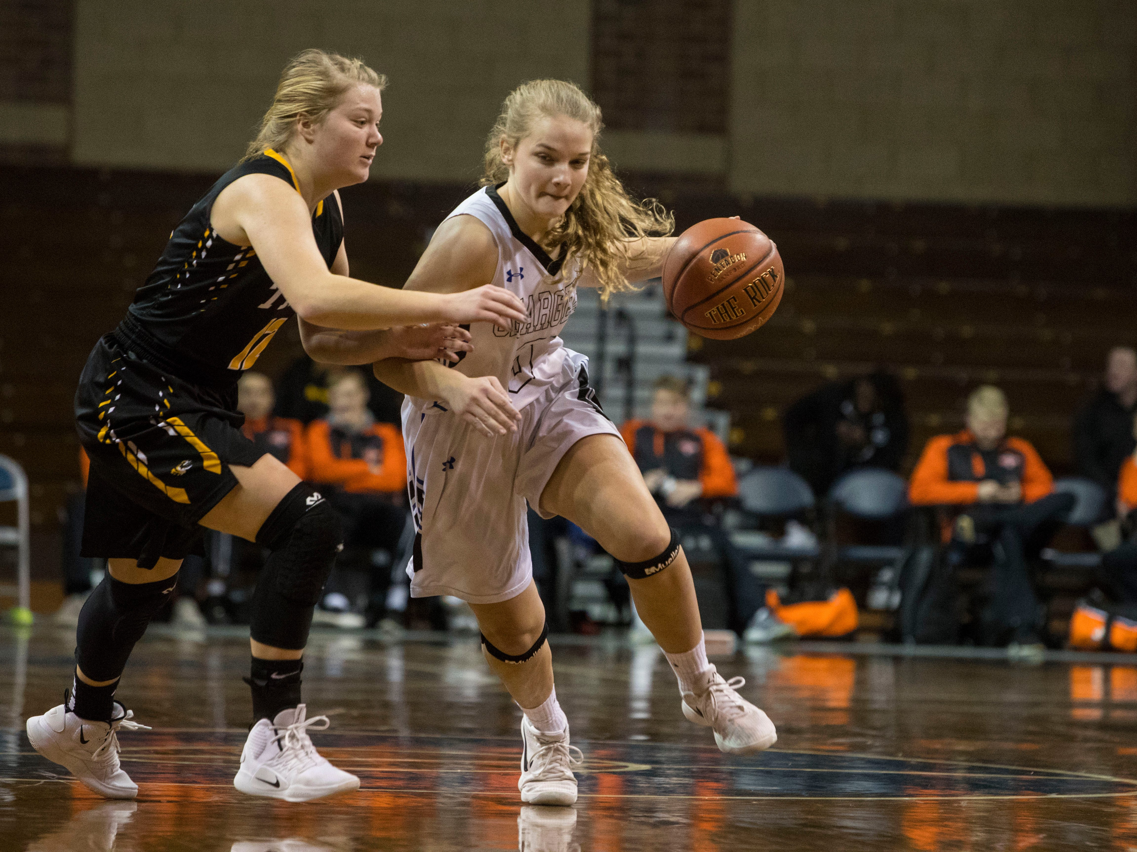 Sioux Falls Christian's Maddie DeJong (5) dribbles the ball past Hutchinson's Michaela Stamer (12) at the Hoop City Classic at the Sanford Pentagon in Sioux Falls, S.D., Saturday, Dec. 29, 2018.
