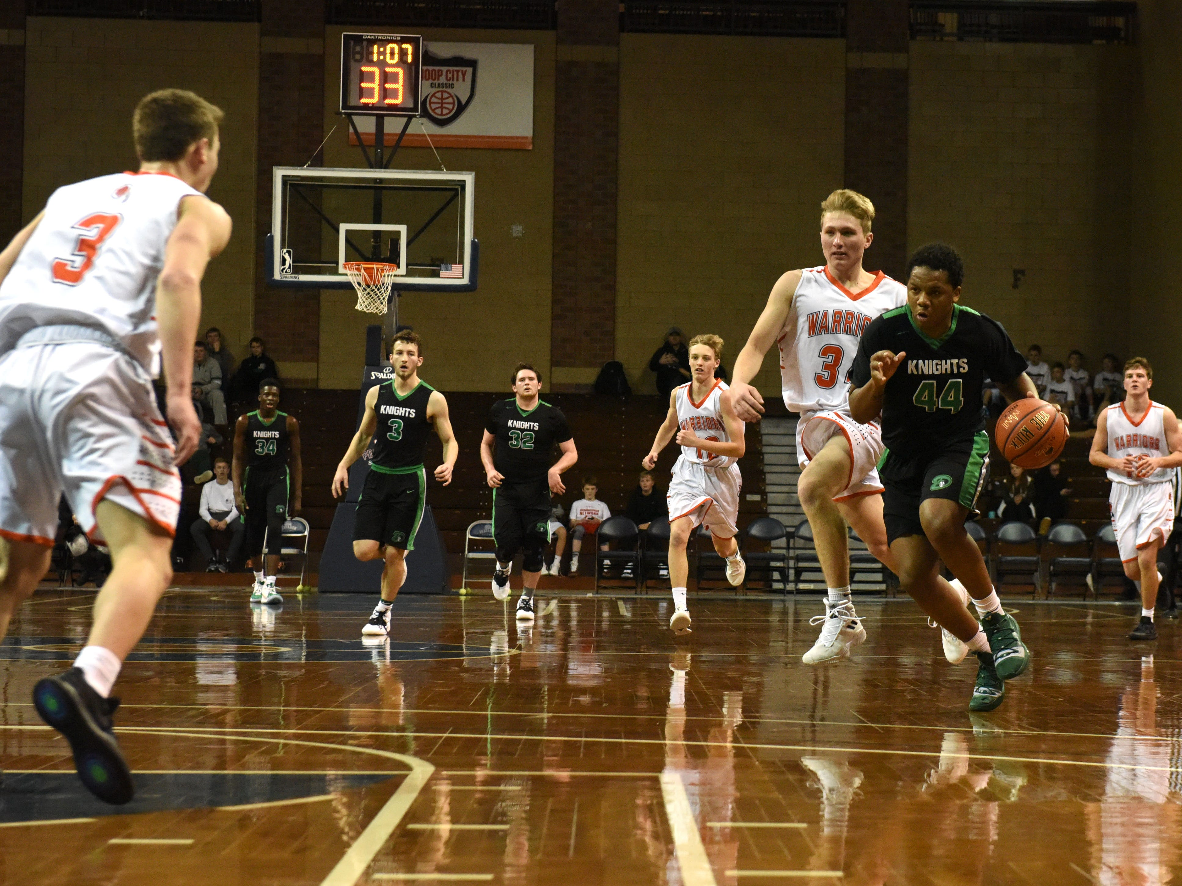 Dominican's Delone Austin (44) dribbles the ball past Washington players at the Hoop City Classic at the Sanford Pentagon in Sioux Falls, S.D., Saturday, Dec. 29, 2018.