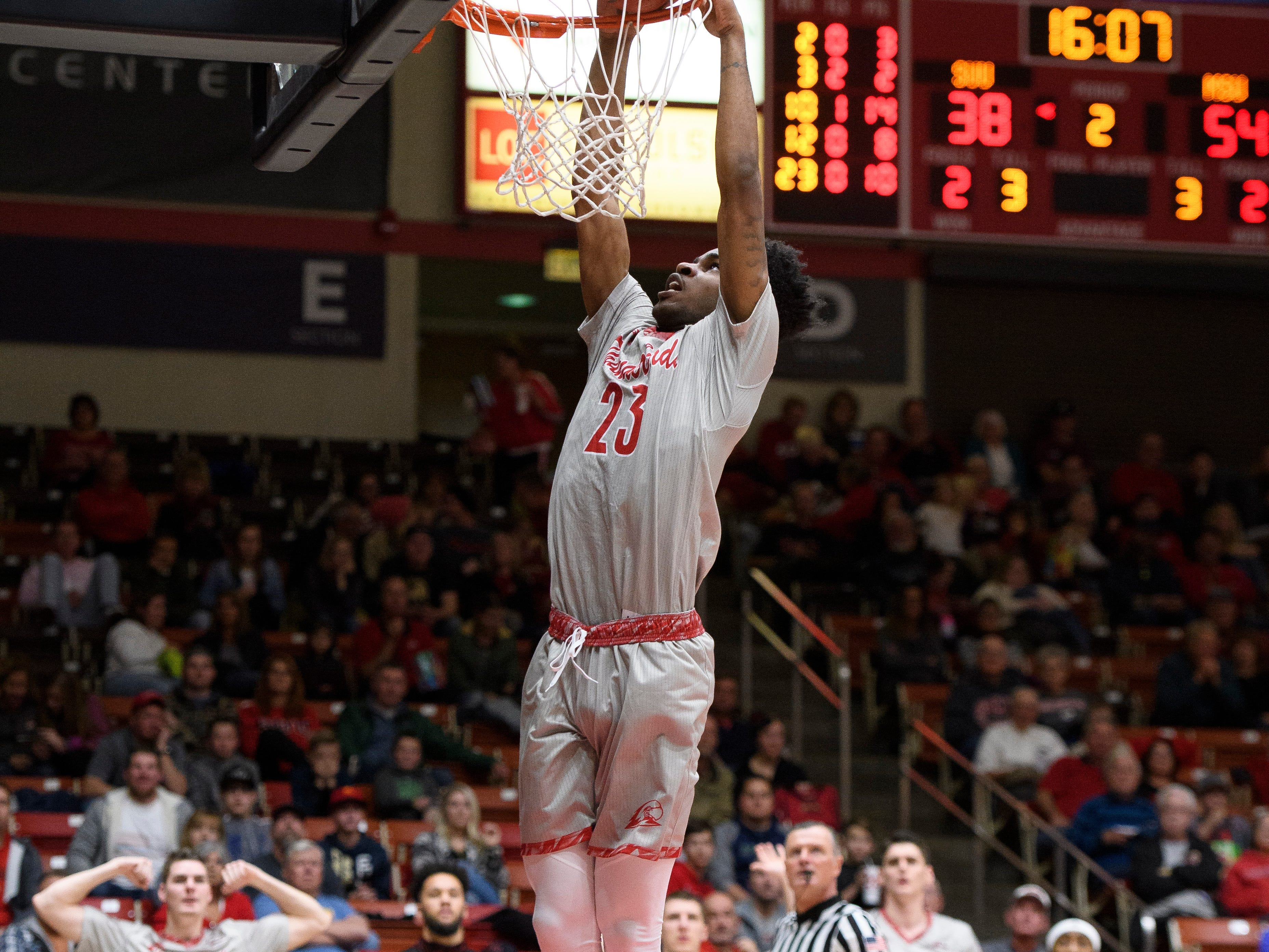 Southern Utah University junior Cameron Oluyitan (23) dunks the ball against Montana State in the America First Event Center Saturday, December 29, 2018. SUU lost, 92-62.