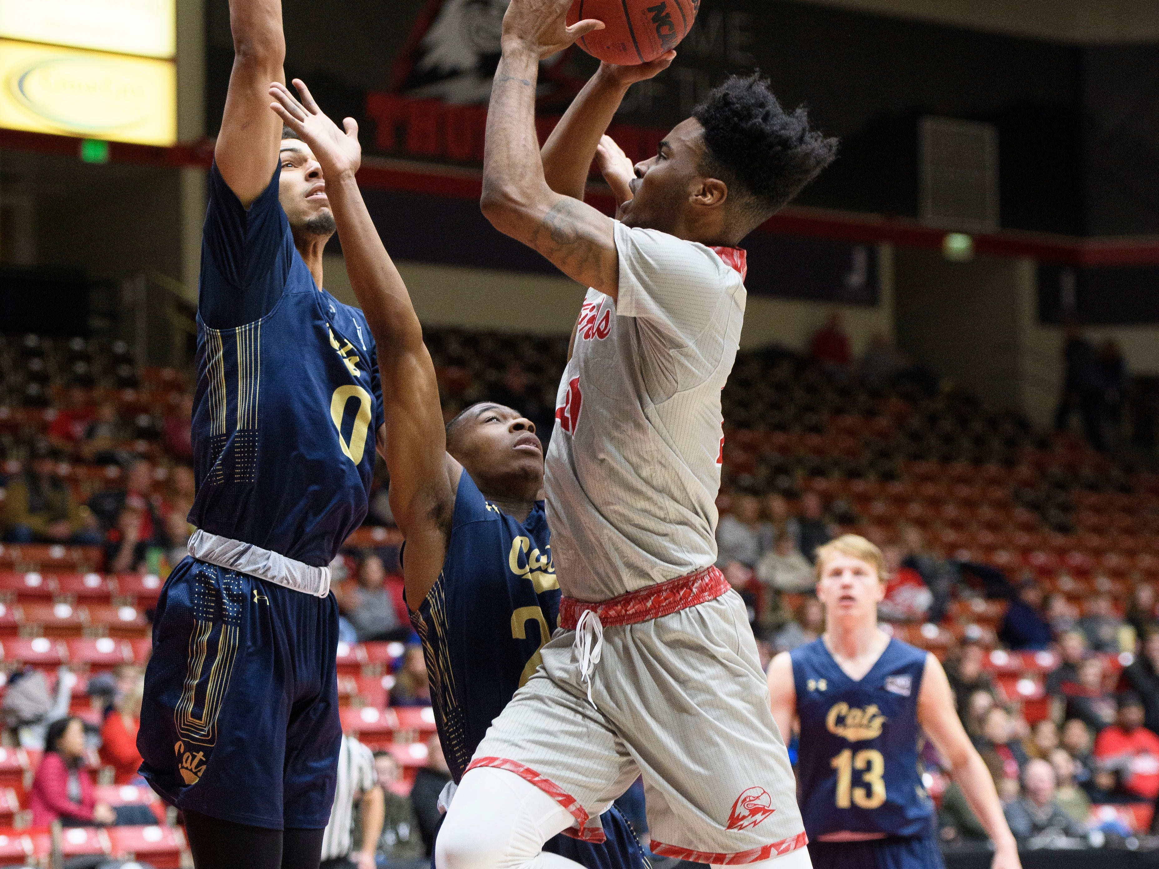 Southern Utah University junior Cameron Oluyitan (23) tries to shoot past two Montana State defenders during the game in the America First Event Center Saturday, December 29, 2018. SUU lost, 92-62.