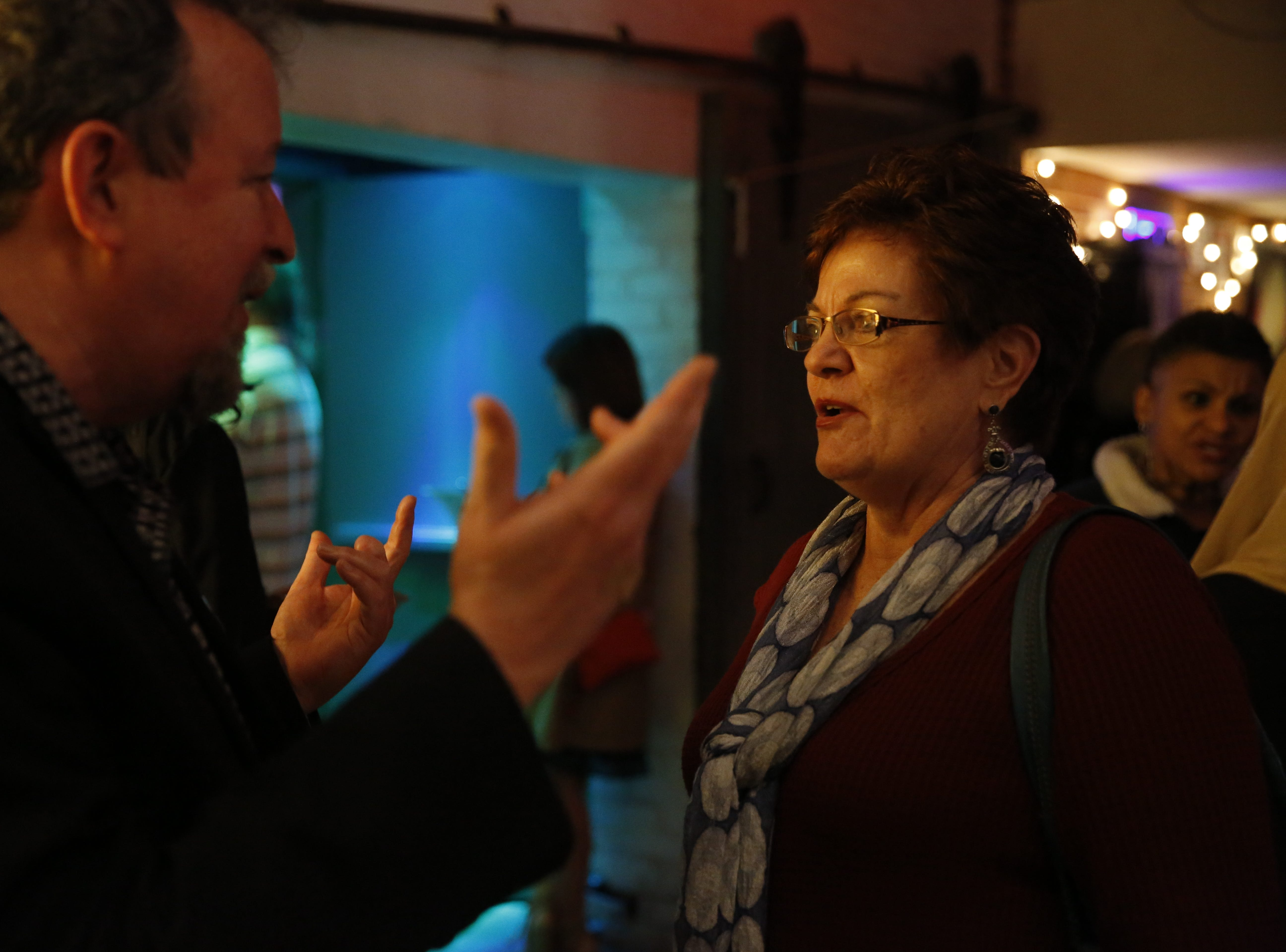 Ellen Eller, right, chats with Tallahassee Democrat journalist Mark Hinson after he told his own story on stage at the Junction at Monroe during the Democrat's first Storytellers night.