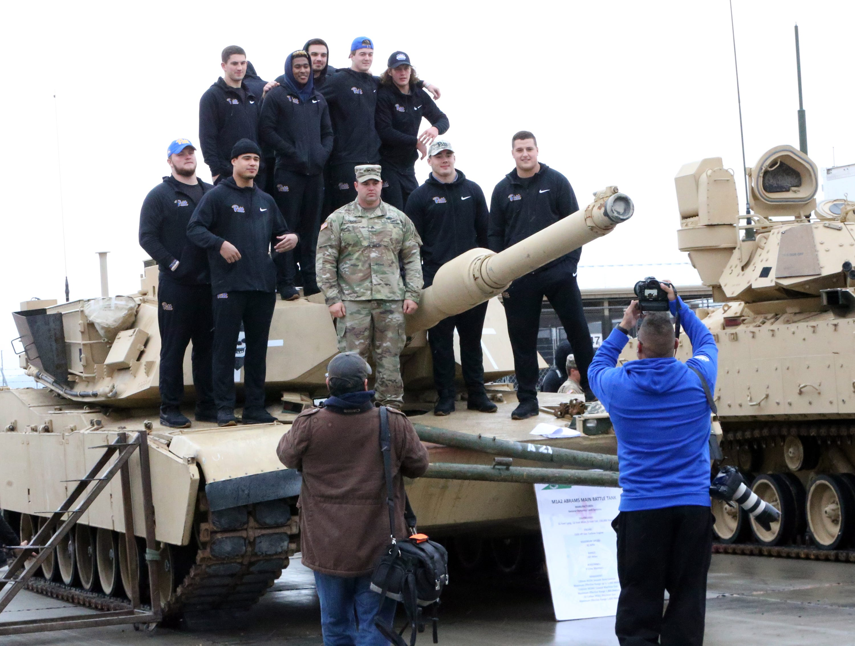 University of Pittsburgh players pose for pictures with a Fort Bliss soldier atop an M1A2 Abrams main battle tank during a visit to Fort Bliss Friday.