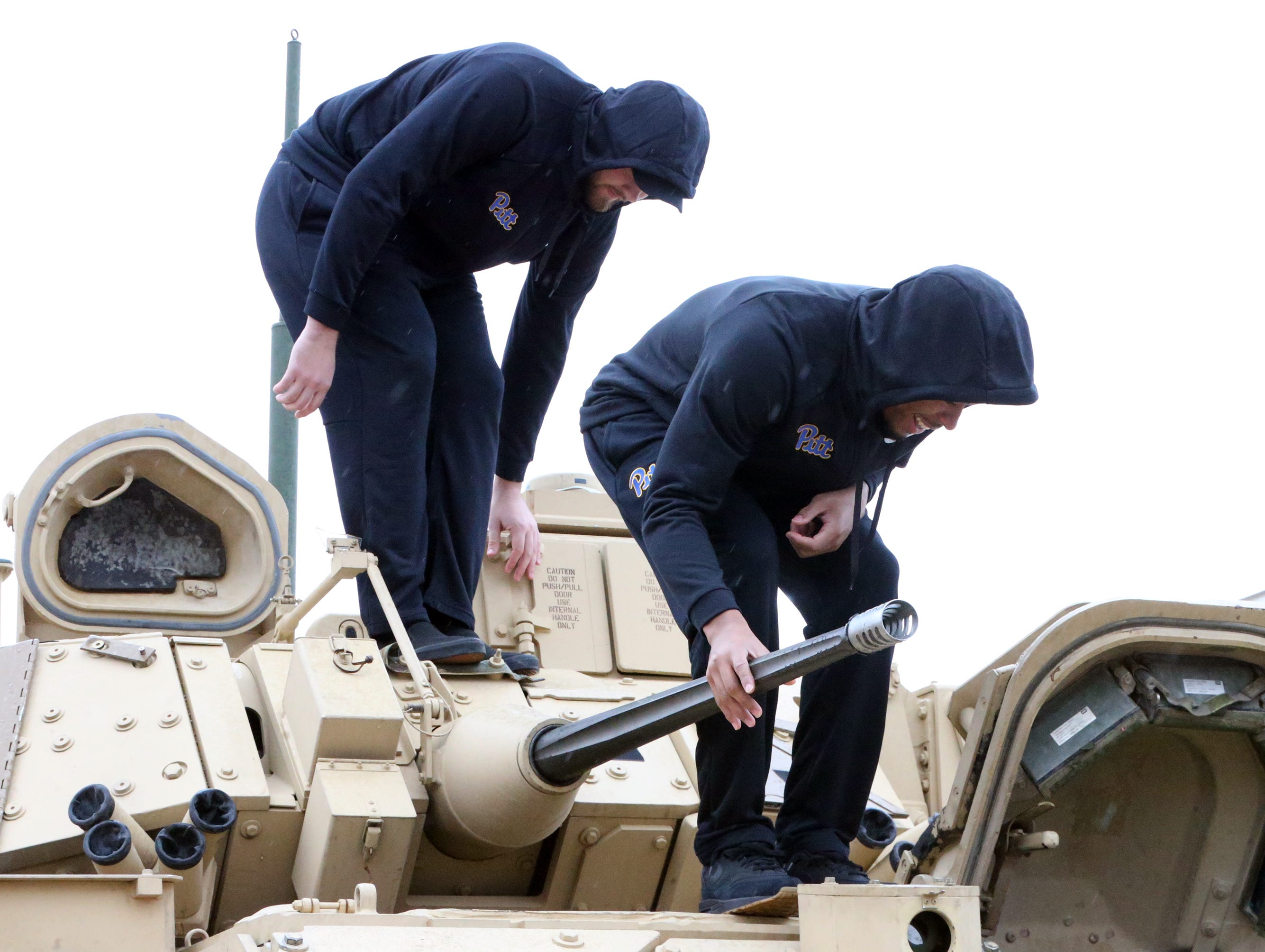 Two University of Pittsburgh football players clamber atop a Bradley Fighting Vehicle Friday a Fort Bliss.