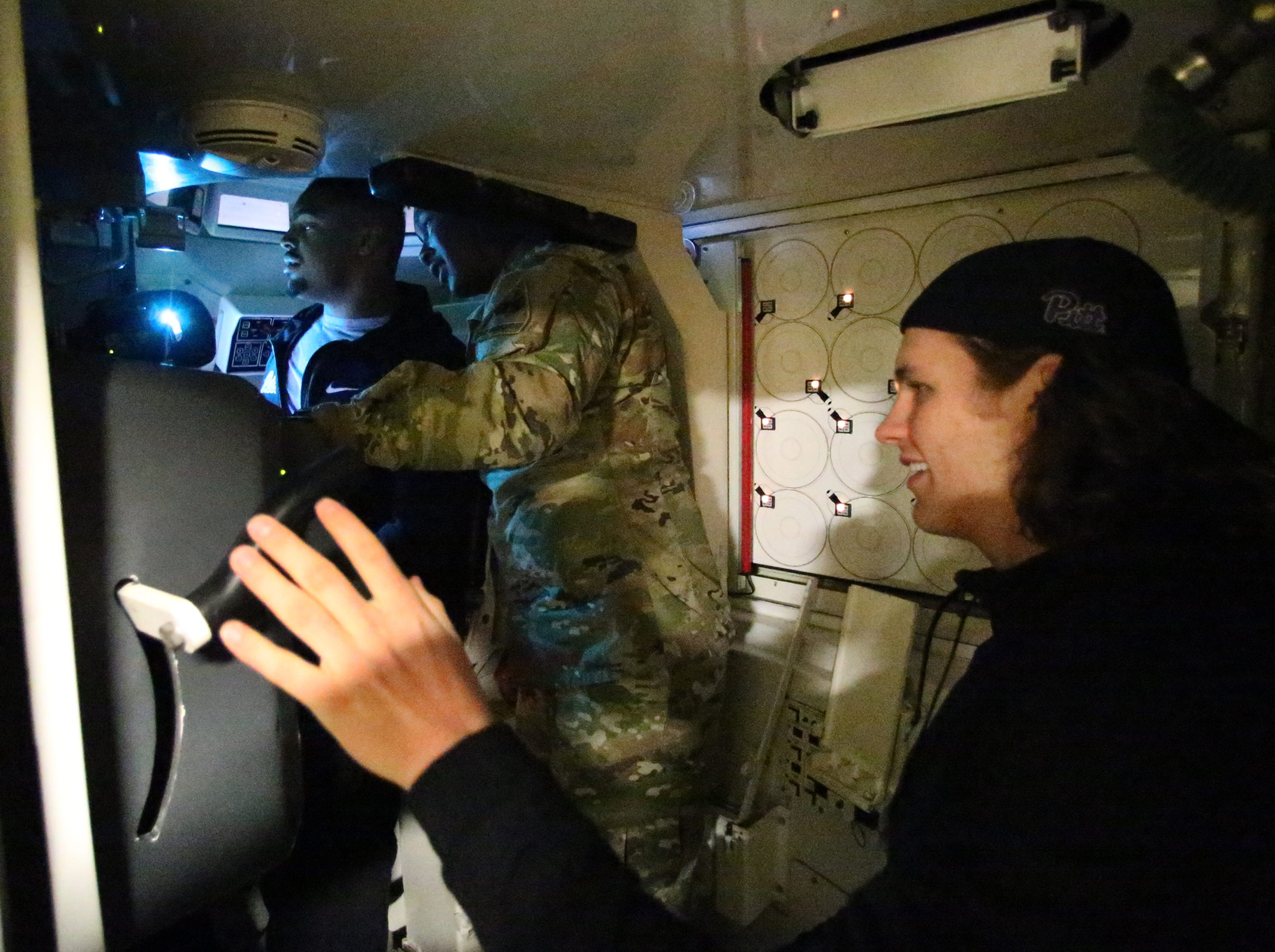 Cal Adomitis, long snapper for the University of Pittsburgh football team operates a simulator with a teammate and help from a soldier Friday at Fort Bliss.