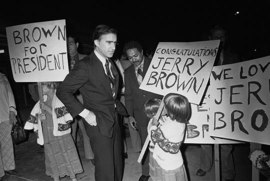 In this May 20, 1976, file photo, California Gov. Edmund G. Brown Jr. is greeted by backers and sign-carrying youngsters upon his return to Sacramento after his victory in the Maryland Democratic presidential primary election. Brown made three unsuccessful attempts for the White House.