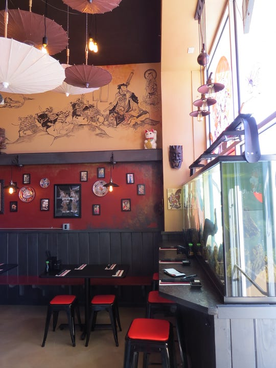 A dining room at Seaward Sushi in Ventura is decorated with murals, paper umbrellas and a newly installed aquarium.