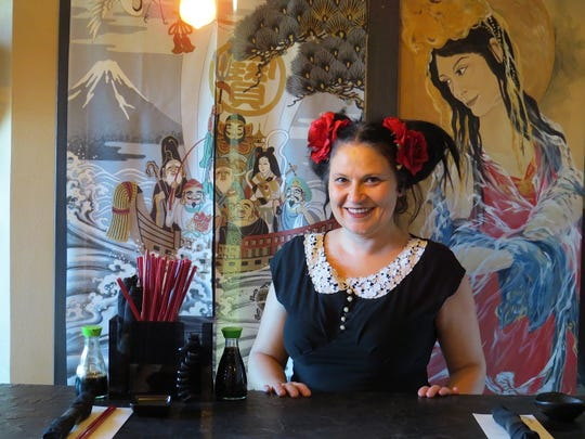 Seaward Sushi owner Rachel Woodward poses with a mural of her mother, one of several family members featured in murals throughout the newly reopened restaurant.