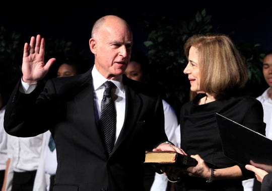 In this Jan. 3, 2011, file photo, Jerry Brown, left, is sworn-in as the 39th governor of California as wife Anne Gust Brown looks on during a ceremony in Sacramento.