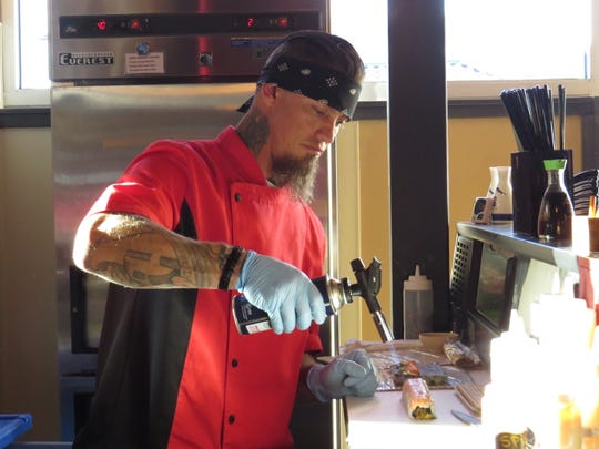 Shane Jones, sushi chef at Seaward Sushi in Ventura, uses a culinary torch to prepare an Atlantis roll featuring asparagus, shrimp and avocado topped with torched salmon.