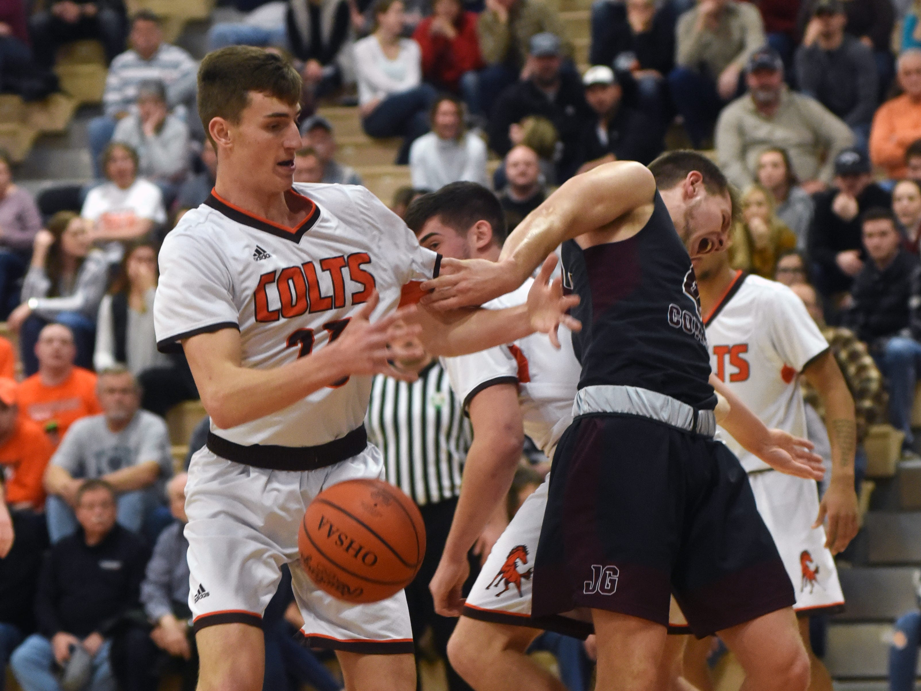 Meadowbrook's Addy Black, left, and John Glenn's Ben Judd get mixed up going for a rebound on Friday night in Byesville.