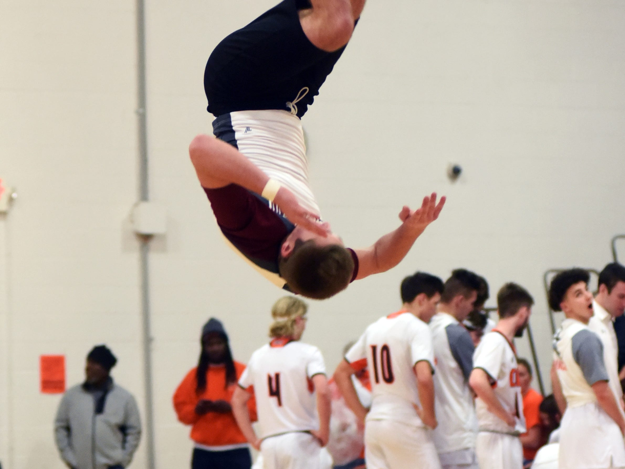 A John Glenn cheerleader does a flip during a timeout on Friday night in Byesville.