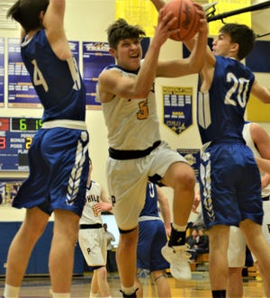 Philo's Cody Butler drives between two Cambridge defenders, Sean Perkins (4) and Ben Ogle (20), in Friday's 46-44 loss.