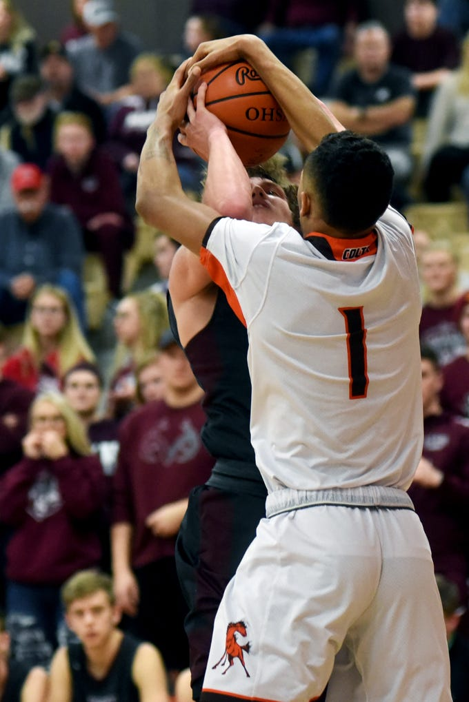 John Glenn's Jack Williams is tied up by Meadowbrook's Johnathan McCall on Friday night in Byesville.
