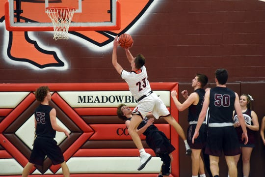 John Glenn's Evan Williams takes a charge from Meadowbrook's Addy Black on Friday night in Byesville.