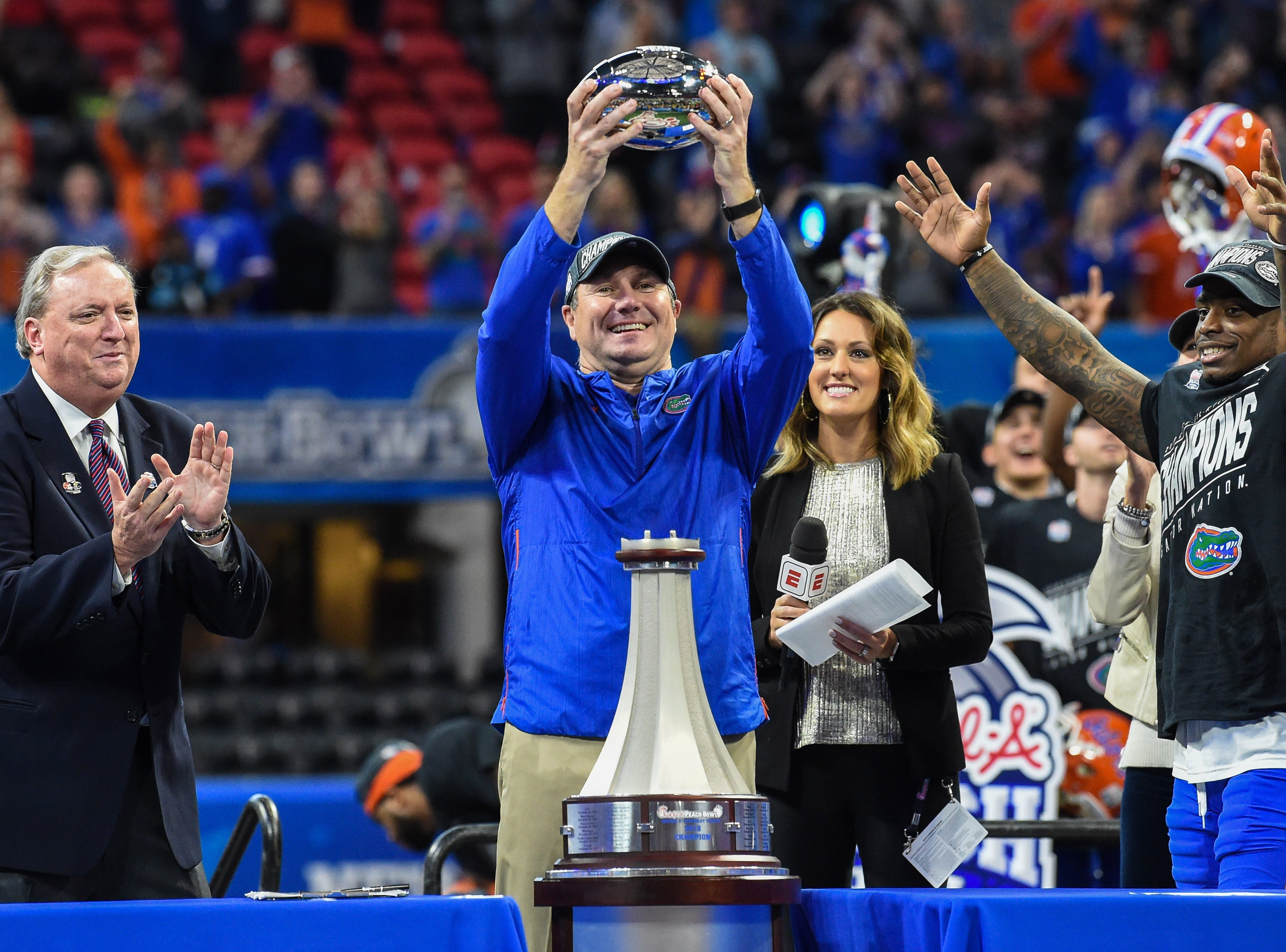 Florida Gators head coach Dan Mullen accepts the trophy after his team defeated the Michigan Wolverines in the Peach Bowl.