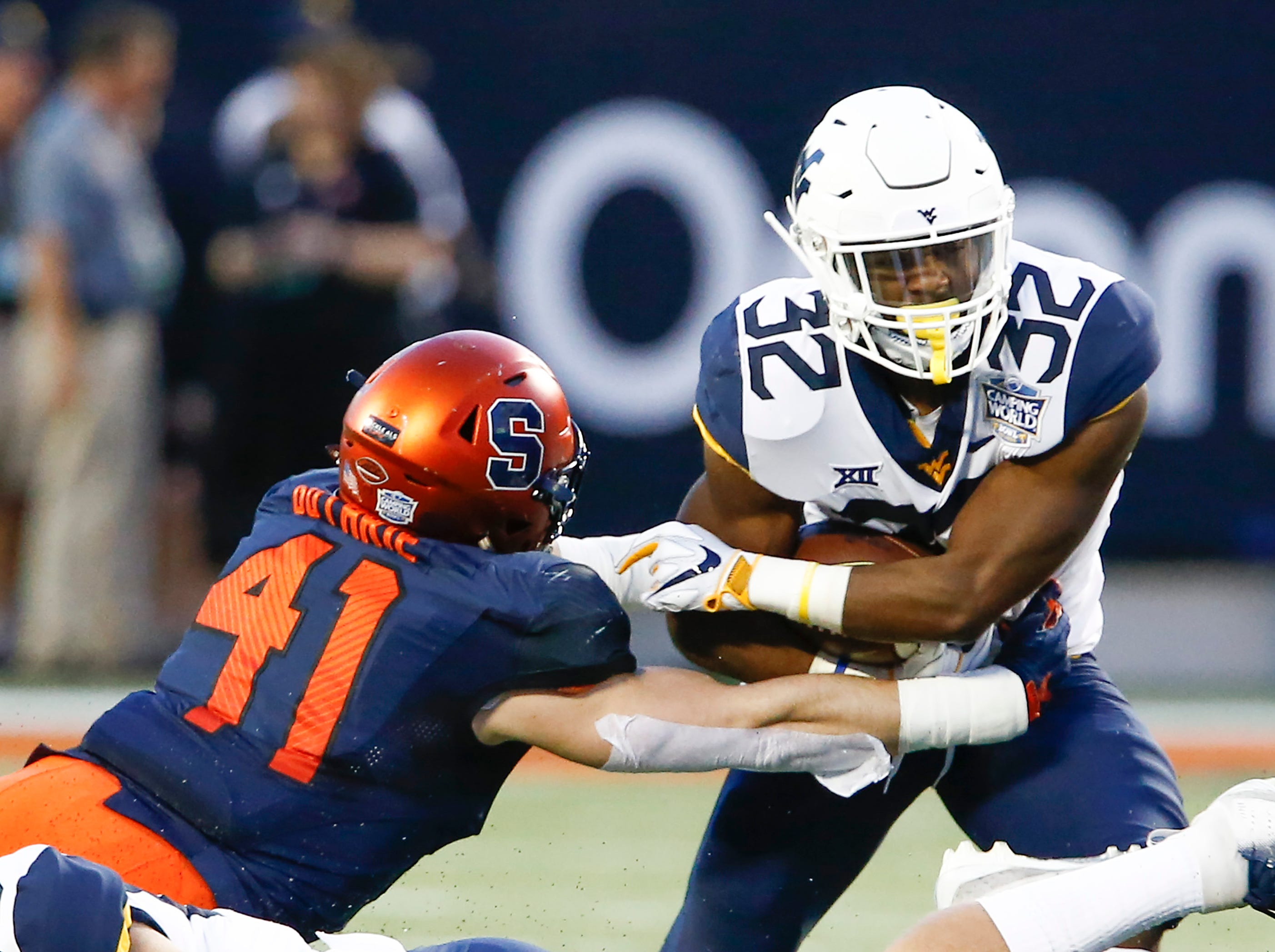 Syracuse Orange linebacker Ryan Guthrie (41) tackles West Virginia Mountaineers running back Martell Pettaway (32) during the first quarter of the Camping World Bowl.