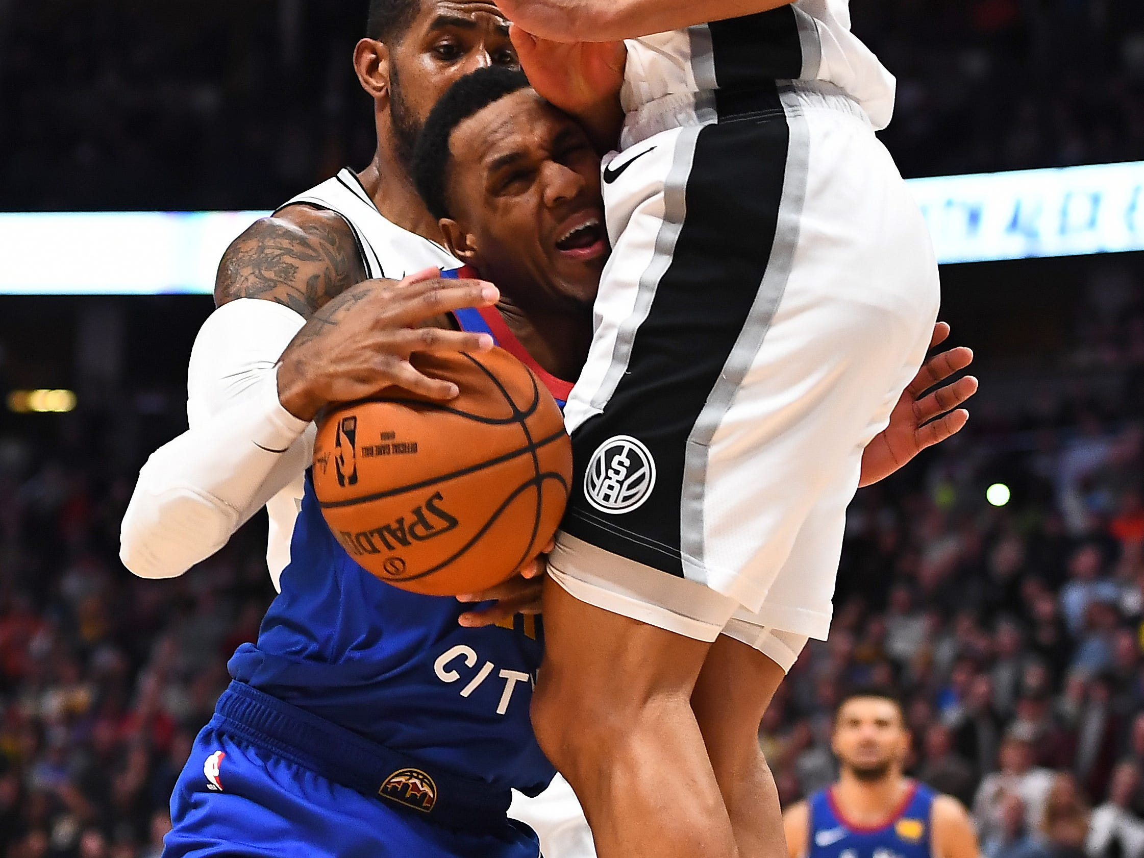 Dec. 28: Nuggets guard Monte Morris (11) collides Spurs defender Bryn Forbes (11) during the second half in Denver.