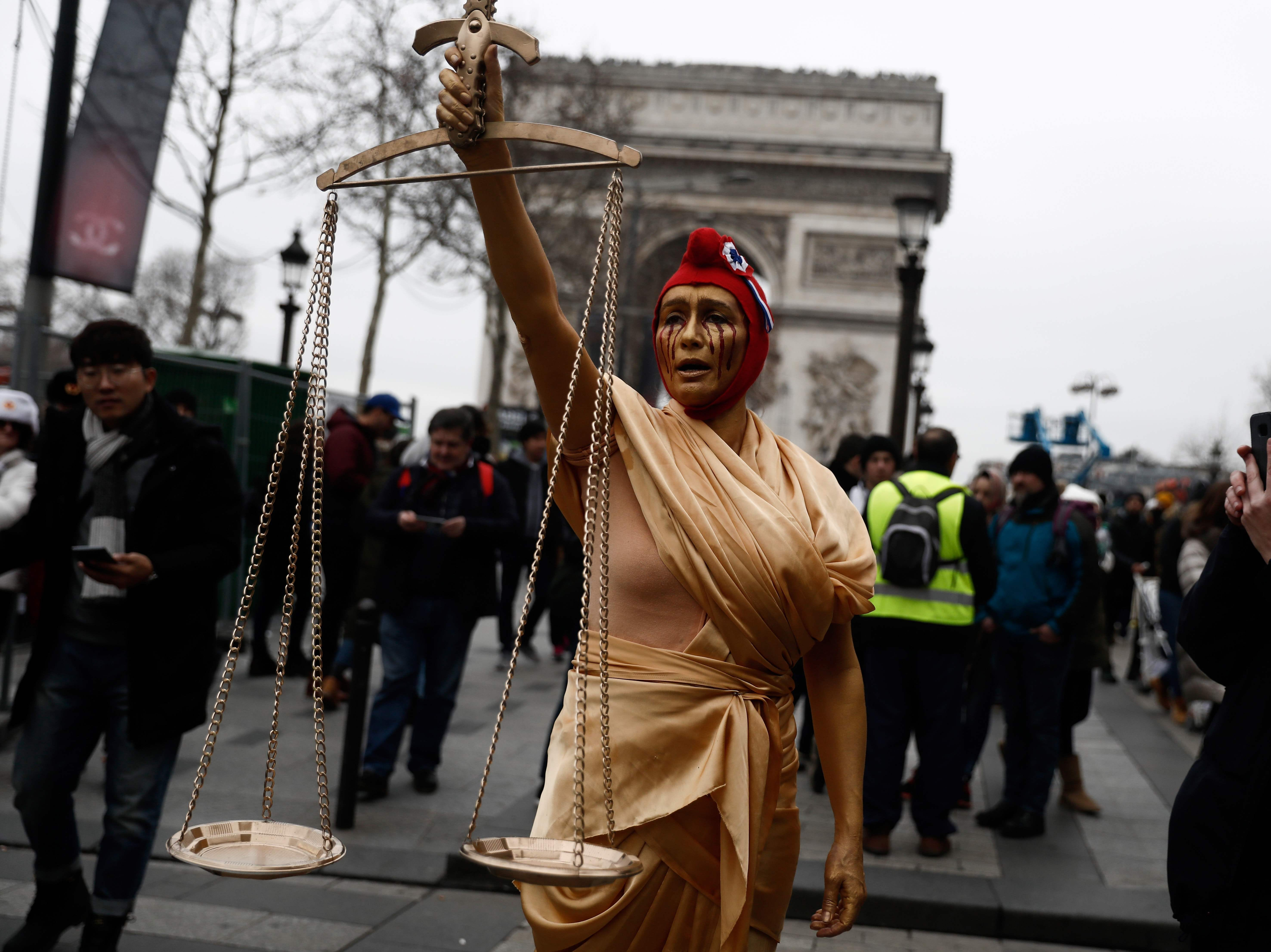 A woman dressed as the Lady Justice and wearing a Phrygian cap walks down the Champs Elysee avenue near the Arc de Triomphe, in Paris, on Dec. 29, 2018 during a demonstration called by the yellow vests (gilets jaunes) movement, to protest against the rising costs of living they blame on high taxes.