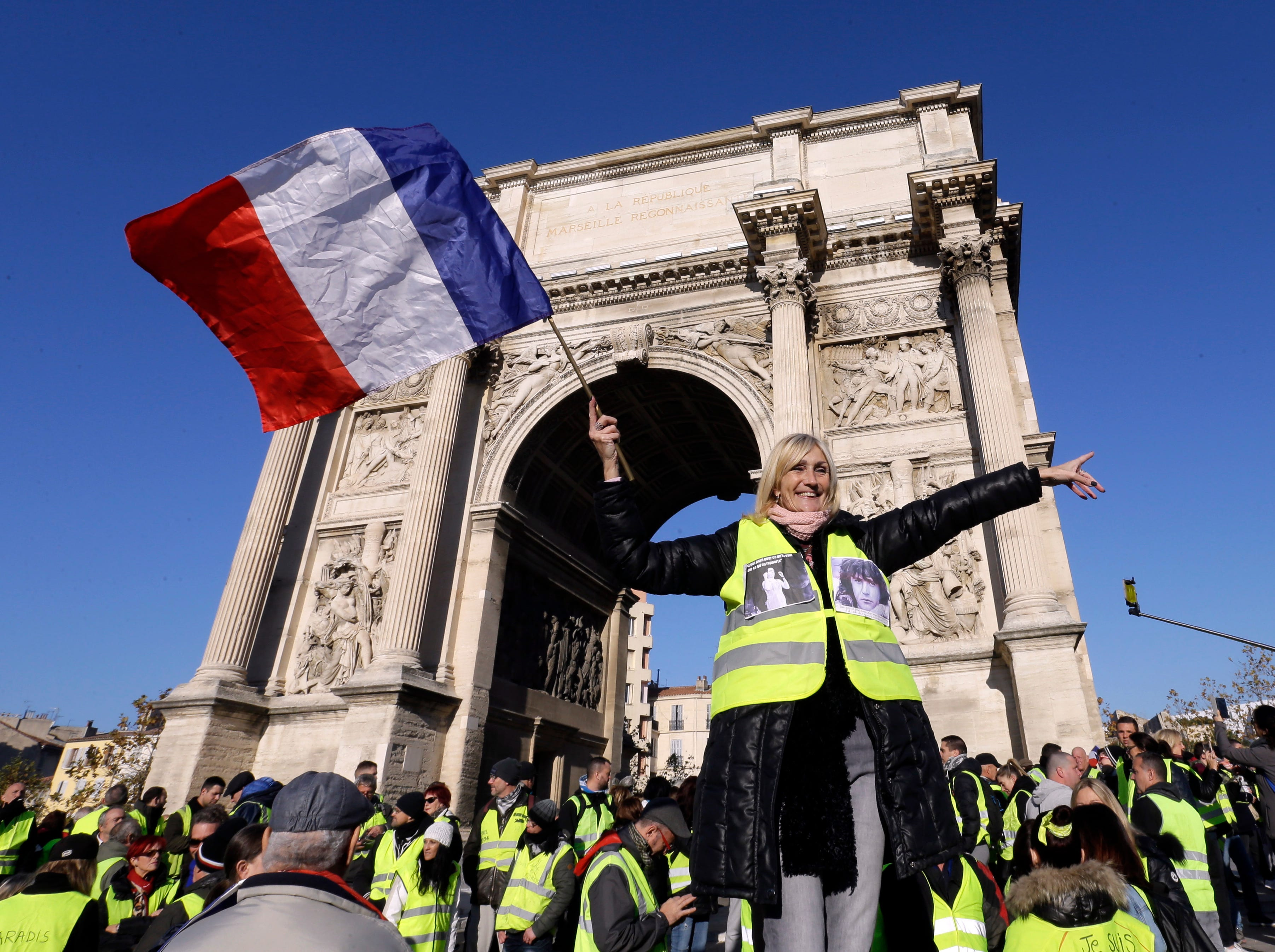 A demonstrator wearing her yellow vest waves a national flag during a protest in front of the Arc de Triomphe of the Porte d'Aix, in Marseille, southern France, Saturday, Dec. 29, 2018.  The yellow vest movement held several peaceful demonstrations in cities and towns around France, including about 1,500 people who marched through Marseille.