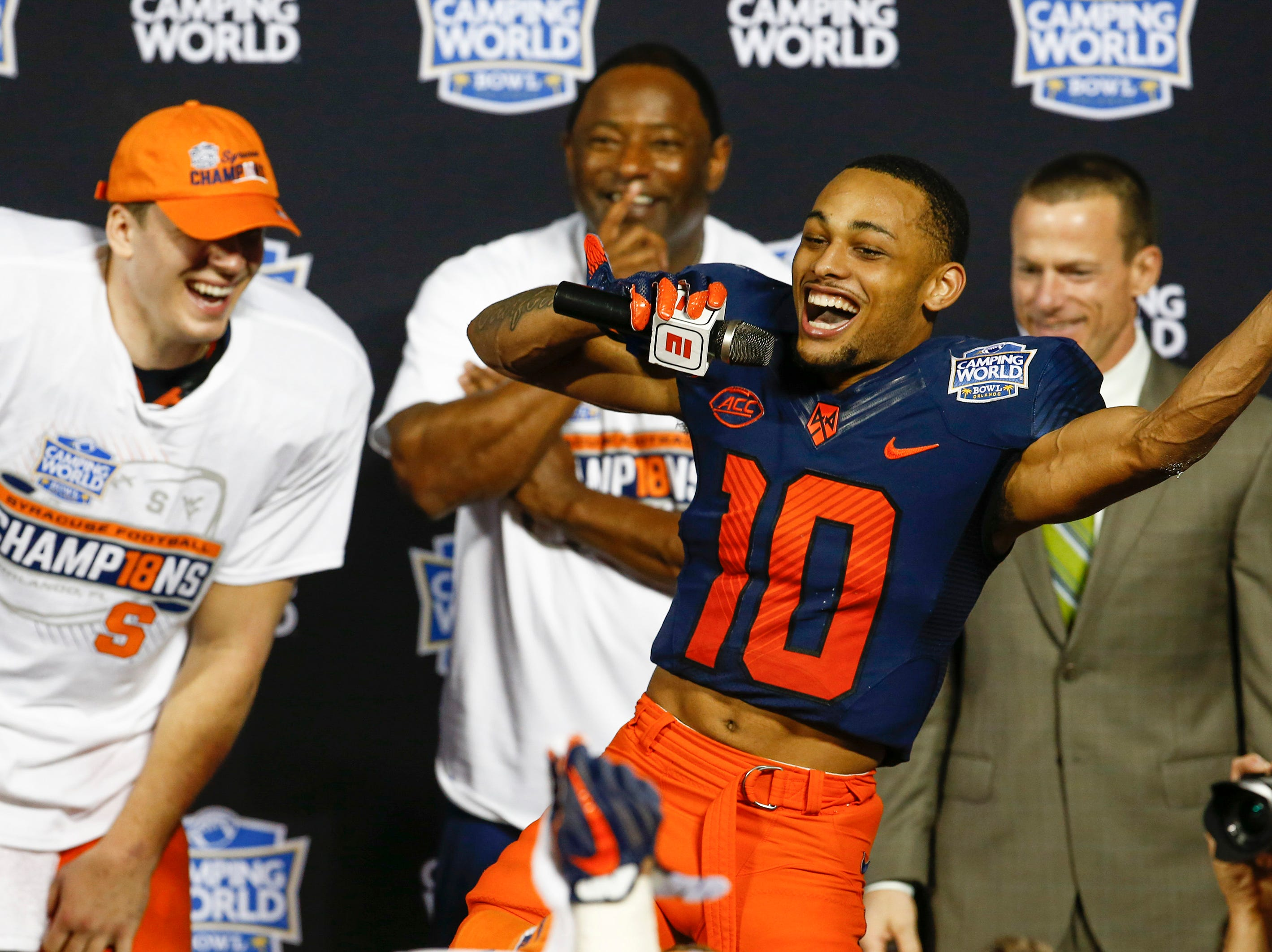 Syracuse Orange quarterback Eric Dungey (left) laughs as wide receiver Sean Riley (10) makes a speech after winning the Camping World Bowl vs. the West Virginia Mountaineers.