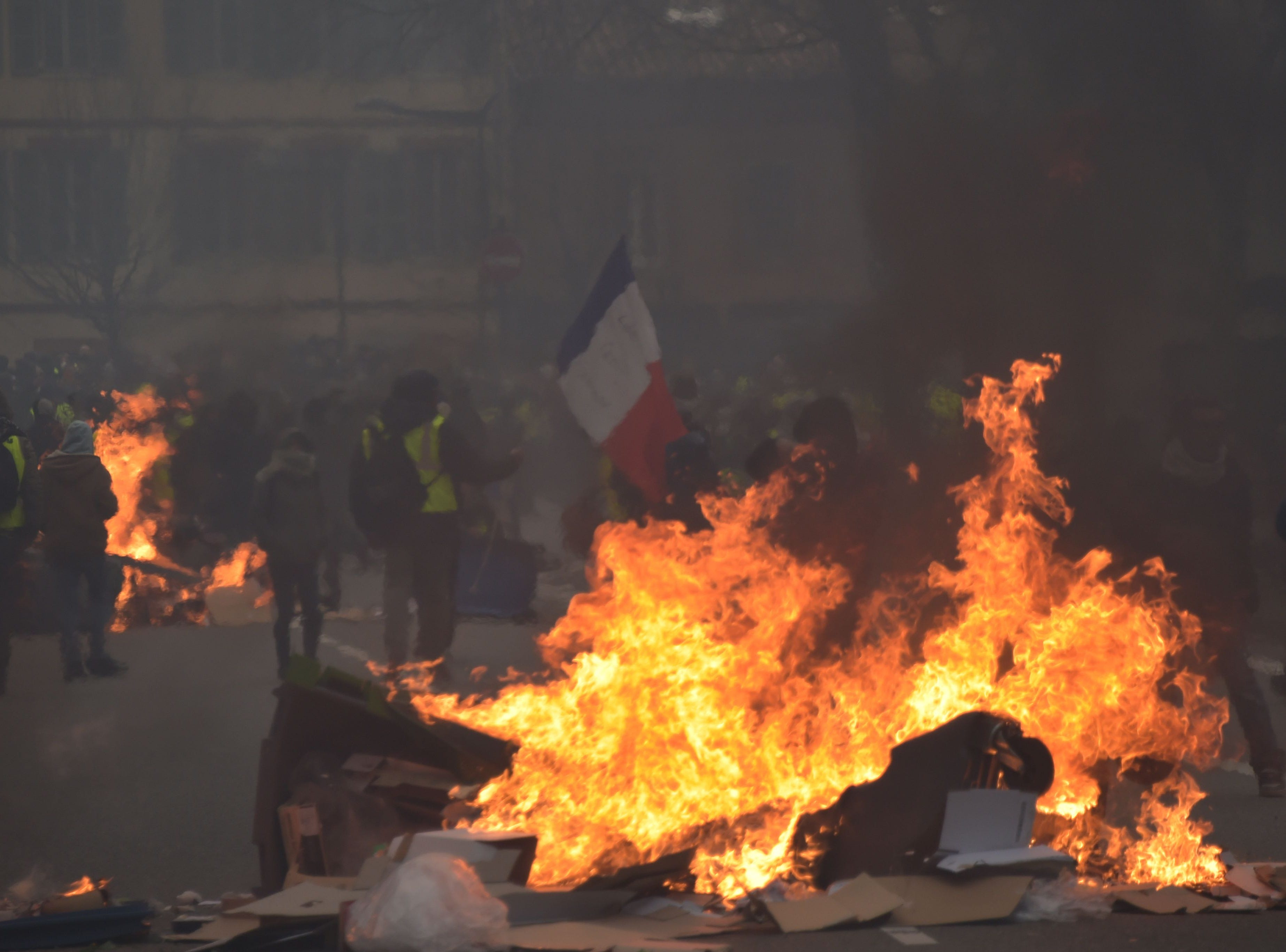 Protestors stand near burning garbage bins during a demonstration called by the yellow vests (gilets jaunes) movement to protest against the rising costs of living they blame on high taxes, on Dec. 29, 2018 in Toulouse, southern France.