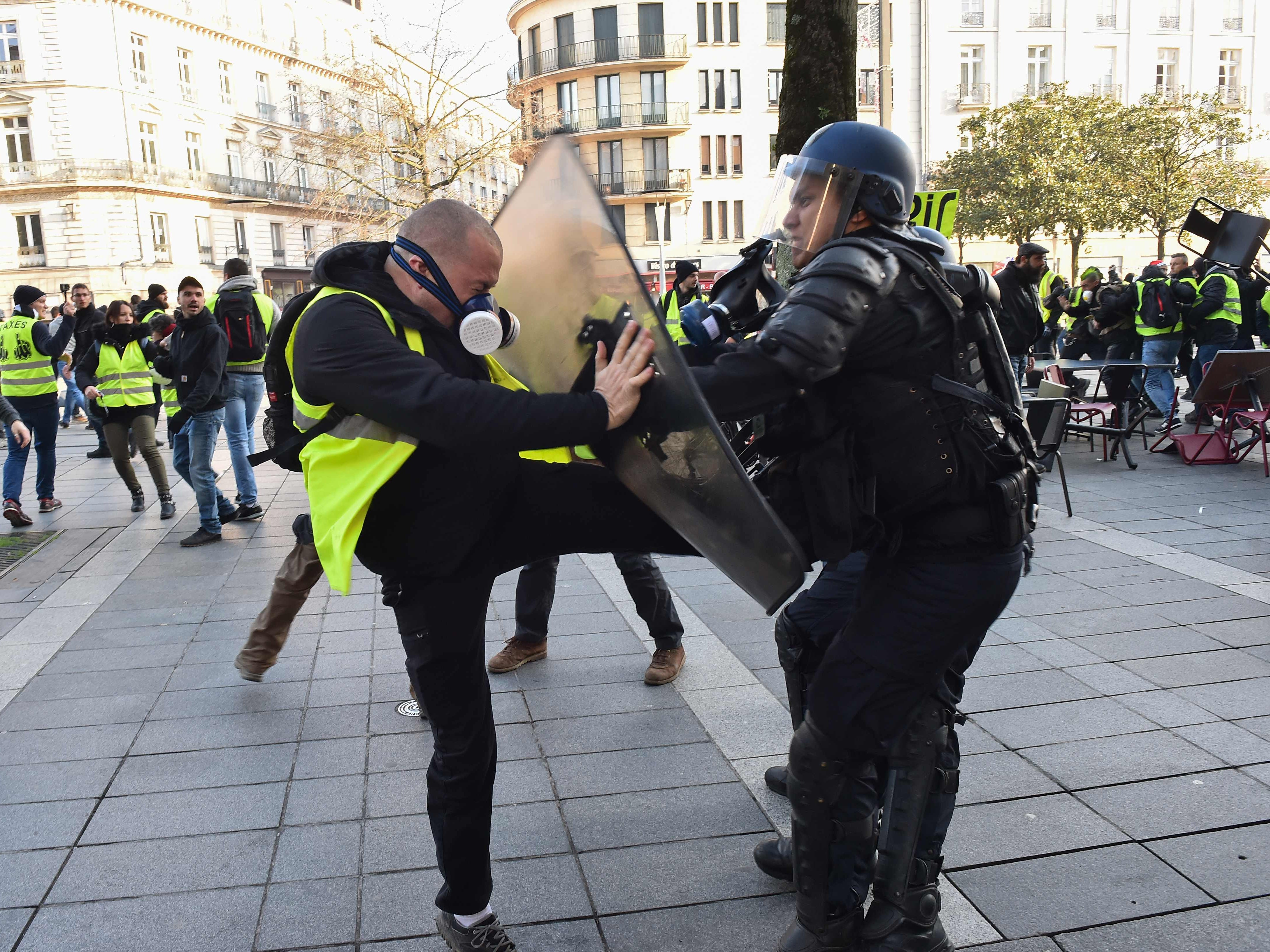 "A protestor wearing a ""yellow vest"" tries to kick a French riot policeman during a demonstration against the rising costs of living, in downtown Nantes, western France, on Dec. 29, 2018."