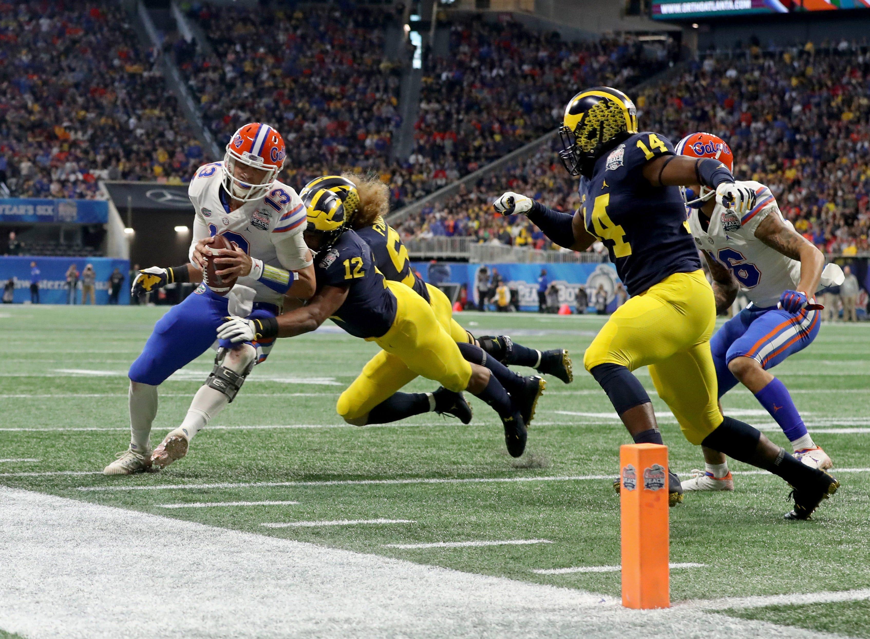 Florida Gators quarterback Feleipe Franks (13) runs against the Michigan Wolverines during the Peach Bowl.