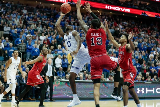 Seton Hall Pirates guard Quincy McKnight (0) lays the ball up as St. John's Red Storm forward Marvin Clark II (13) and guard Justin Simon (5) defend