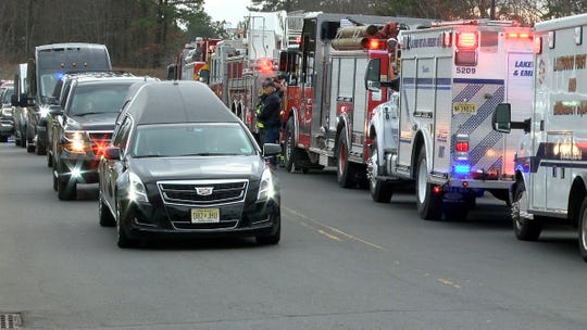 The hearse carrying Victor Lugo past emergency vehicles and through the Lakewood Public Works facility Sunday, December 30, 2018, enroute to his nearby funeral services.  Lugo, who worked at the Public Works, was among the four men killed in a crash on the Garden State Parkway early Wednesday morning.