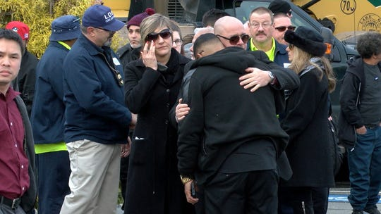 Marlon Rivera, Jackson, shares a hug, while Jennifer Bulk, Jackson, wipes away a tear after Victor Lugo's funeral procession stopped at the Lakewood Public Works facility Sunday, December 30, 2018, enroute to his nearby funeral services.  Lugo, who worked at the Public Works, was among the four men killed in a crash on the Garden State Parkway early Wednesday morning.