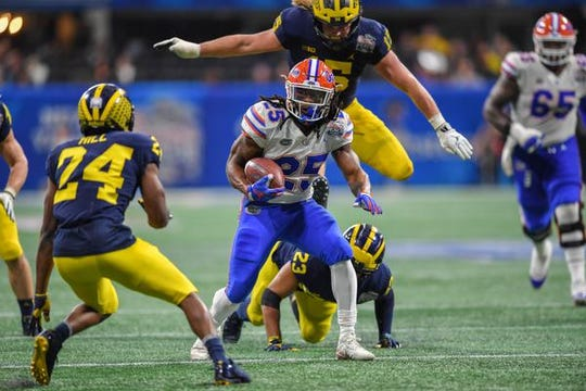 Florida Gators running back Jordan Scarlett (25) breaks tackles running with the ball against the Michigan Wolverines as Jawaan Taylor (65) trails the play   during the second half at Mercedes-Benz Stadium.