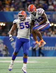 Florida Gators defensive tackle Kyree Campbell (55) and defensive back Chauncey Gardner-Johnson (23) celebrate a play in the second quarter against the Michigan Wolverines in the 2018 Peach Bowl at Mercedes-Benz Stadium.