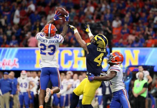Florida Gators defensive back Chauncey Gardner-Johnson (23) intercepts a pass intended for Michigan Wolverines wide receiver Nico Collins (4) as Florida Gators defensive back Trey Dean III (21) is shown on the play during the third quarter in the 2018 Peach Bowl at Mercedes-Benz Stadium.