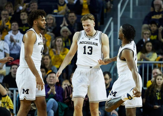 Michigan forward Ignas Brazdeikis, center, is congratulated by forward Isaiah Livers, left, and guard Zavier Simpson after scoring during the second half of U-M's 74-52 win on Sunday, Dec. 30, 2018, at Crisler Center.