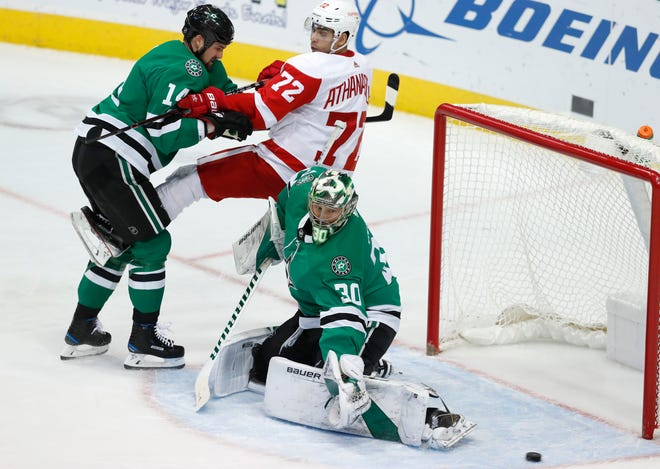 Detroit Red Wings center Andreas Athanasiou is tied up by Dallas Stars left wing Jamie Benn, as goaltender Ben Bishop (30) reaches for a shot on goal during the first period in Dallas, Saturday, Dec. 29, 2018.
