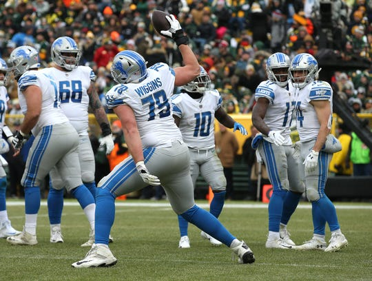 Lions offensive lineman Kenny Wiggins spikes the ball in celebration after a touchdown run by Zach Zenner during the first half on Sunday, Dec. 30, 2018, in Green Bay, Wis.
