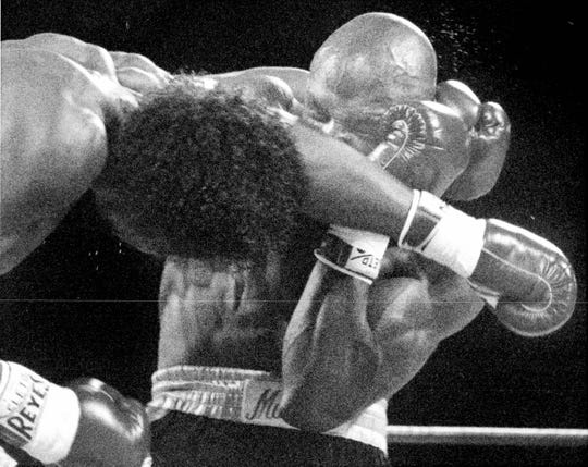 Thomas Hearns loops a left that slides off Marvin Hagler's glove in the first round of their bout in 1985 in Las Vegas.