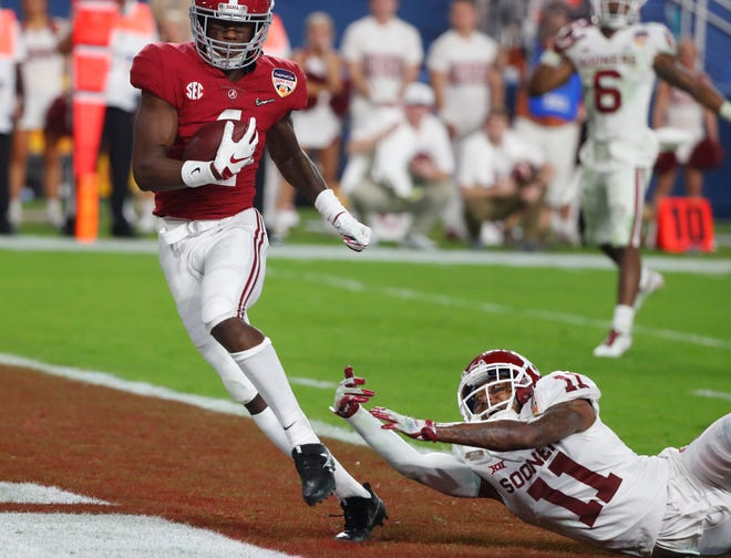 Alabama wide receiver Jerry Jeudy (4) scores a touchdown ahead of a tackle by Oklahoma cornerback Parnell Motley (11) during the second half.