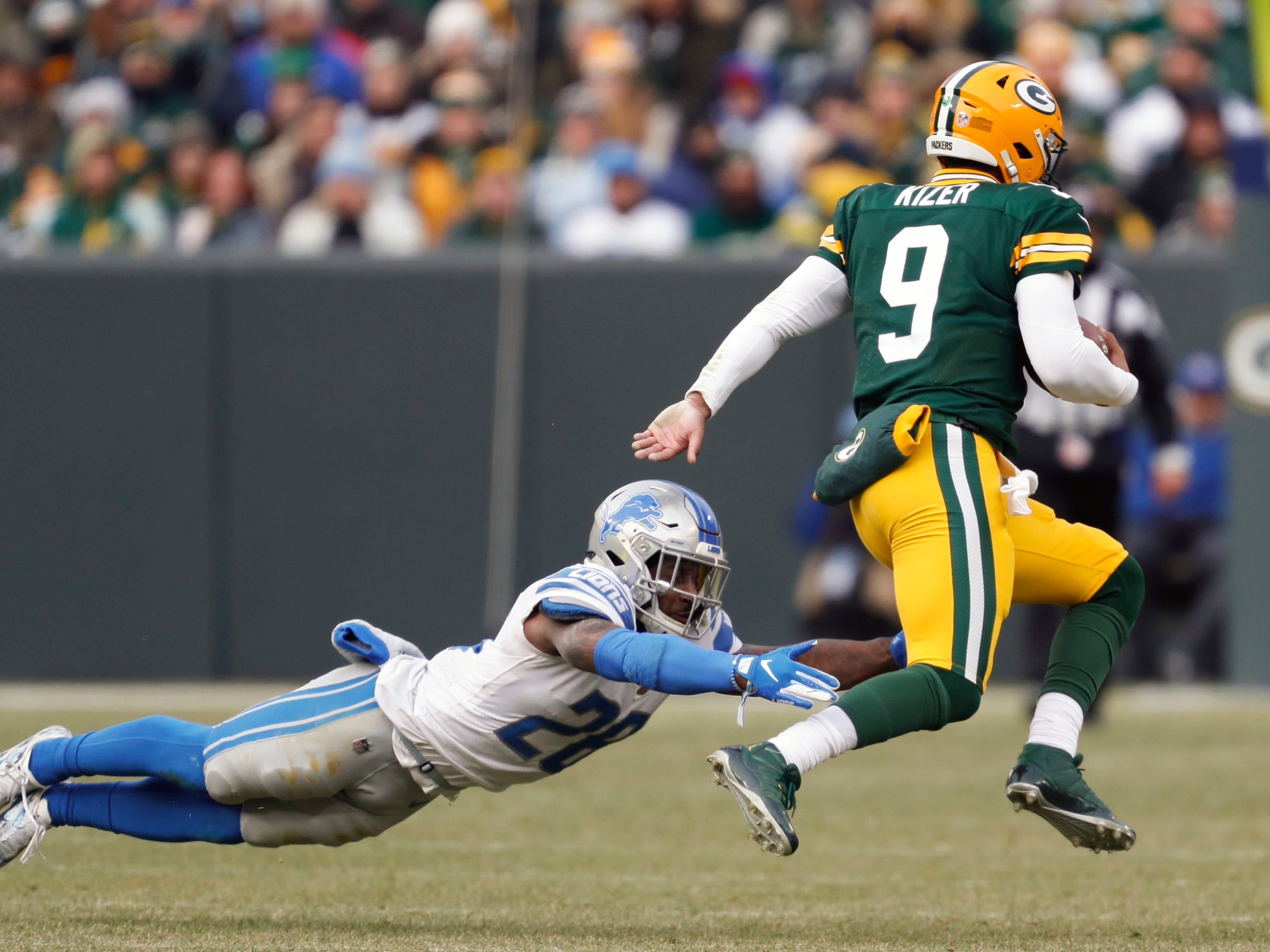 Green Bay's DeShone Kizer runs for a first down past Detroit's Quandre Diggs during the second half.